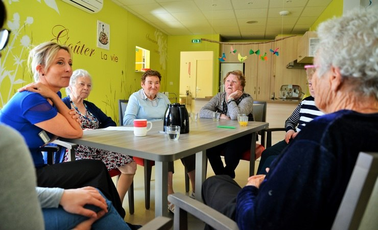 Personnes âgées autour d'une animatrice à l'accueil de jour