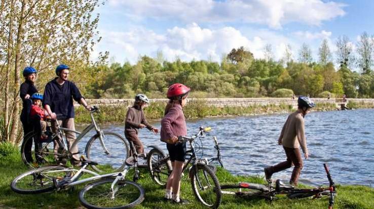 Famille à vélo au bord d'un étang