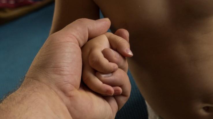 Main d'adulte tenant la main d'un jeune enfant