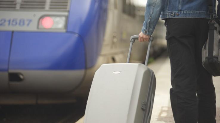 Jeune avec une valise sur le quai d'une gare pour un voyage éducatif à l'étranger