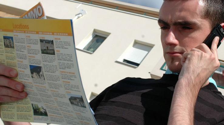 Jeune au téléphone cherchant à louer un logement