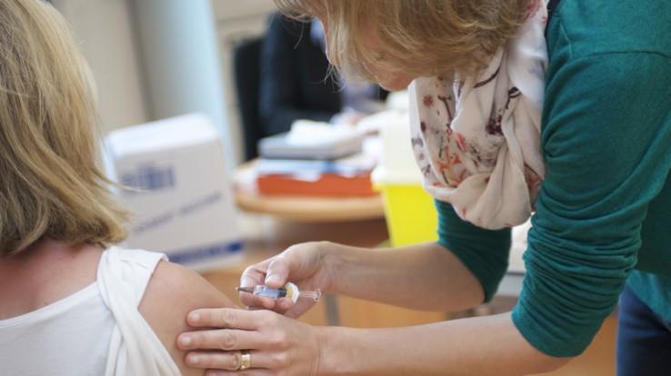 Une femme se fait vacciner dans le bras