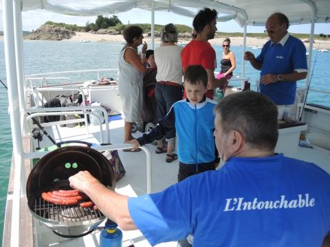 Un œil sur le bateau, un œil sur la cuisson. À la fois organisateur, chef-cuisinier et animateur, Luc veille à ce que la journée soit un succès pour tout le monde.