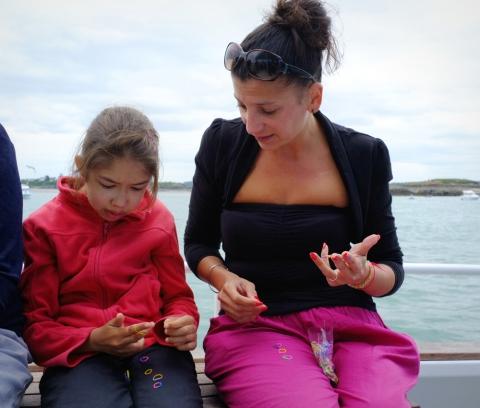 Même sur l'eau on n'échappe pas au phénomène de mode. Laurianne fait une démonstration de confection de bracelet à Myriam.