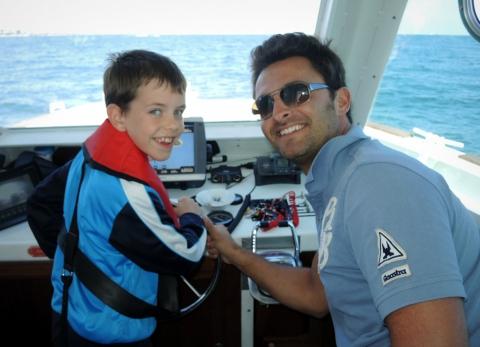 Yanis, 8 ans et demi, à la barre de L'Intouchable. À ses côtés, Freddy est bénévole pour Merlib depuis déjà cinq ans.