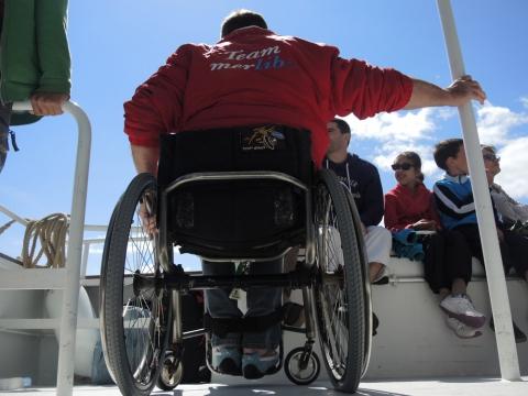 Un large pont permet à Luc et aux autres personnes en fauteuil de pouvoir circuler aisément sur le bateau. On notera l'absence de freins sur le fauteuil du président. Une philosophie.