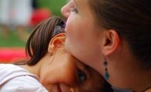 Petite fille dans les bras d'une assistante familiale