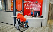 Personne en fauteuil roulant à l'accueil de la Mdph