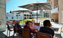 Personnes âgées assises en terrasse dans un établissement d'hébergement temporaire