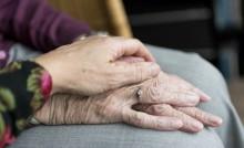 Main d'un aidant posée sur les mains d'une personnes âgées