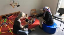 Assistante sociale montre un livre à un enfant