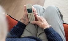 Personne âgée avec un téléphone pour signaler une situation de maltraitance