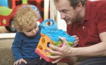 Un père montre un jeu à son enfant