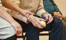 Une aide à domicile tient une personne âgée par le bras