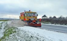 Saleuse au travail sur une route enneigée